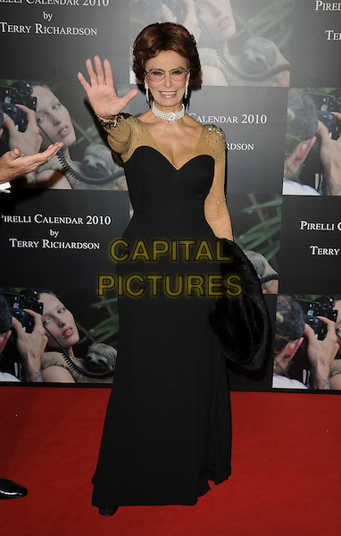 SOPHIA LOREN .At the 2010 Pirelli Calendar Cocktail Reception and Gala Dinner, Old Billingsgate Market, London, England, UK, November 19th 2009..full length black strapless long maxi dress gold sleeves beaded sheer see thru through mesh sparkly hand waving .CAP/CAN.©Can Nguyen/Capital Pictures.