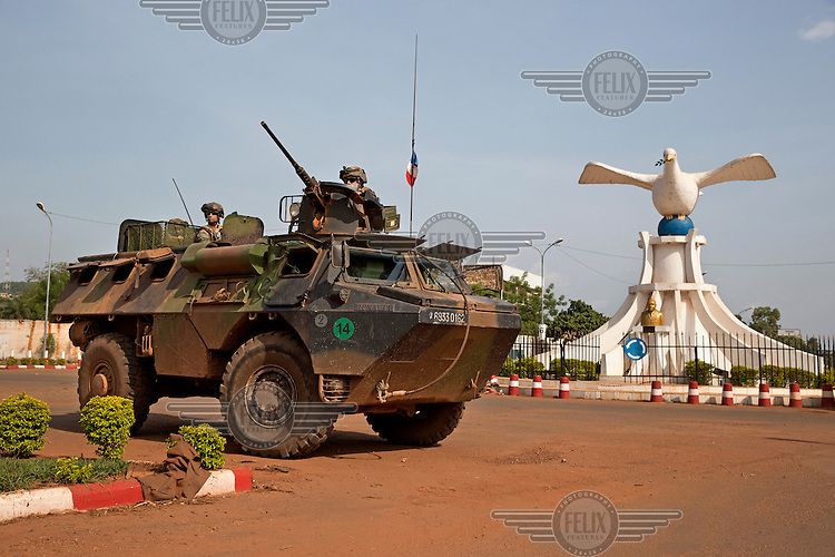French peacekeepers aboard an armoured vehicle patrol past a statue of a 'dove of peace' on the airport road.In late 2012 after years of instability and conflict, the Seleka, a predominantly Muslim rebel group, fuelled by grievances against the government, overran the country and, In March 2013, ousted President Francois Bozize, who fled the country. The rebel's leader Michel Djotodia was proclaimed president in August 2013. He disbanded the Seleka in September 2013 but law and order collapsed and ex-Seleka fighters roamed the country committing atrocities against the civilian population. In an attempt to defend their lives and property vigilante groups, calling themselves Anti-Balaka (Anti-Machete), formed to confront the ex-Seleka fighters but soon began to take reprisals against the wider Muslim population and the conflict became increasingly sectarian. By December 2013, with international fears of a genocide being voiced, French led peacekeepers deployed to the country began to act on a UN mandate to disarm the fighters and protect the civilian population. However, they have struggled to contain the situation. Much of the Muslim population, in particular, have been forced into ghettos where they are suffering from food shortages and limited access to healthcare. Often, only a few peacekeepers stand between them and a massacre by vengeful Anti-Balaka militants. UN reports describe 'thousands' killed, while over 600,000 people have been internally displaced and a further 200,000 have fled the county.