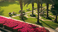 .Dubai, United Arab Emirates. Royal Mirage Hotel. Arabian style formal garden with guests on sunbeds..