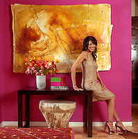 Portrait of designer Suzanne Boyd against a bright pink wall with a gold artwork