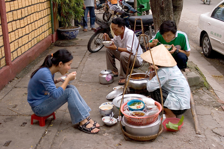 Vietnamese typically eat their family meals on the streets.  This scene occuring in Hue, central Vietnam.