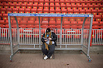 A visiting fan making use of a spare dug out at the Gateshead International Stadium, the athletics stadium which is also the home ground of Gateshead FC,  the club played host to Cambridge United in a Blue Square Bet Premier division fixture. The match ended in a one-all draw, watched by a crowd of 904. The point meant Gateshead went to the top of the division, one below the Football League in England.