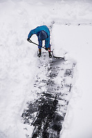 Adult shoveling snow after winter storm.