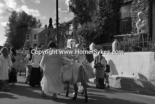 Hunting the Earl of Rone. Combe Martin Devon   England. 2011. The procession through the village, the Earl of Rone sitting on a donkey facing backwards.