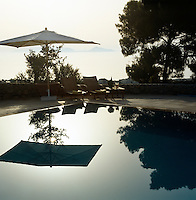 The swimming pool is set in a circular terrace which overlooks the village and the sea beyond