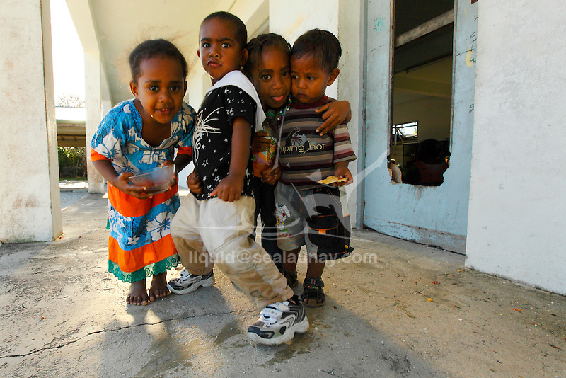 """Children in  the mission establish in 1969 in the Fayaoue village on the Ouvea island in the Loyalty islands..Ouvéa (local pronunciation: [u've.a]) is a commune in the Loyalty Islands Province of New Caledonia, an overseas territory of France in the Pacific Ocean. The settlement of Fayaoué [fa'jawe], on Ouvéa Island, is the administrative centre of the commune of Ouvéa..Ouvéa is made up of Ouvéa Island, the smaller Mouli Island and Faiava Island, and several islets around these three islands. All these lie among the Loyalty Islands, to the northeast of New Caledonia's mainland..Ouvéa Island is one of the Loyalty Islands, in the archipelago of New Caledonia, an overseas territory of France in the Pacific Ocean. The island is part of the commune (municipality) of Ouvéa, in the Islands Province of New Caledonia..The crescent-shaped island, which belongs to a larger atoll, is 50 km (30 miles) long and 7 km (4.5 miles) wide. It lies northeast of Grande Terre, New Caledonia's mainland..Ouvéa is home to around 3,000 people that are organized into tribes divided into Polenesian, Melanesian and Walisian by ethnic descend. The Iaai language is spoken on the island..The two native languages of Ouvéa are the Melanesian Iaai and the Polynesian Faga Uvea, which is the only Polynesian language that has taken root in New Caledonia. Speakers of Faga Uvea have fully integrated into the Kanak society, and consider themselves Kanak..Ouvéa has rich marine resources and is home to many sea turtles, species of fish, coral as well as a native parrot, the Uvea Parakeet, that can only be found on the island of Ouvéa..A large crustacaen called a """"coconut crab"""" or crabe de cocotier can also be found on the islands. The large crabs live in palm tree plantations and live solely on a diet of coconuts that they crack open with their powerful claws. They are blue in colour and can grow to several kilos in size. They are a land based species and do not venture into the ocean..Ouvéa is also home to t"""