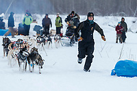 Trail volunteer Erica Goad runs in front of Ray Redington Jrs. team to a parking spot at the Nikolai checkpoint during the 2018 Iditarod race on Tuesday March 06, 2018. <br /> <br /> Photo by Jeff Schultz/SchultzPhoto.com  (C) 2018  ALL RIGHTS RESERVED