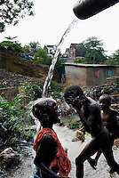 Kroo Bay, Freetown, Sierra Leone...Story on child and maternal health in the Kroo Bay slum community in Freetown, Sierra Leone, which has the World's worst infant and maternal mortalitly rates. One in 4 children die before they reach the age of 5 and one in 6 mothers dies during child birth (in the UK, the rate is one in 3,800)...The Kroo Bay Community Health Centre has a catchment area of over 8,000 people but lacks adequate facilites to provide even basic care. The clinic lacks even the basics, such as bedpans, surgical spirits and cotton wool. It has no electricity and clean drinking water must be fetched from the nearby well everyday...Children wash in the stream of a water pipe...© 2007 Aubrey Wade. All rights reserved.