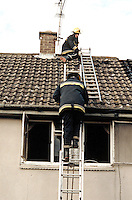 Firefighter on roof of a house on fire he is in the process of smashing a hole in it in an attempt to let out the heat and smoke. This image may only be used to portray the subject in a positive manner..©shoutpictures.com..john@shoutpictures.com