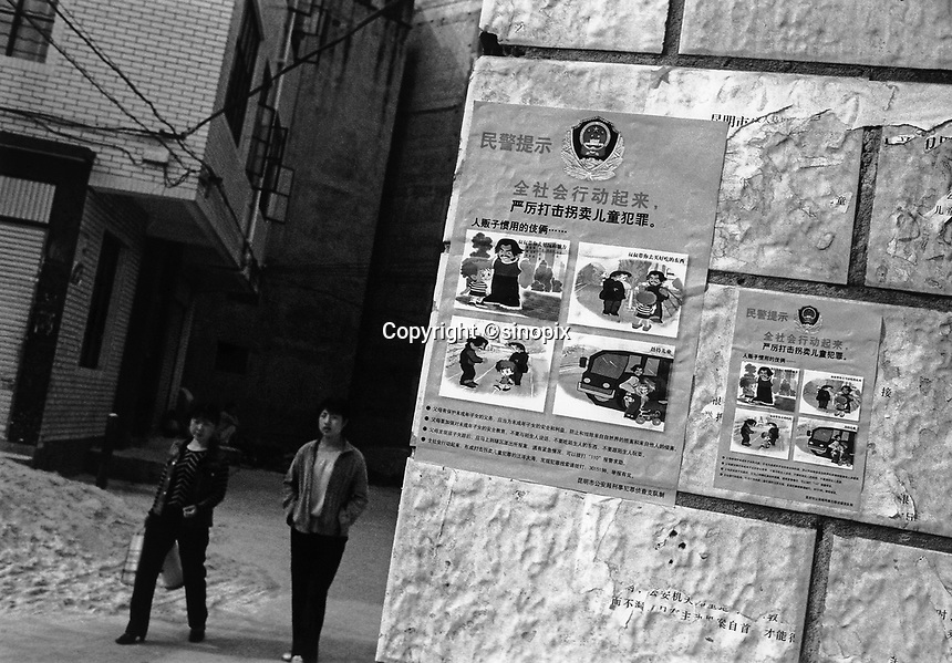 Posters on a wall in the Guangdu district of Kunming City, China, warn parents of the human trafficers gangs that prey on the young boys in the area. Thousands of migrant mothers' children have been stolen and sold to rich families desperate for a boy.  Families are limited to a single child under the China's ruthless One Child Policy.<br /> 30 Jul 2004<br /> <br /> photo by Richard Jones / Sinopix