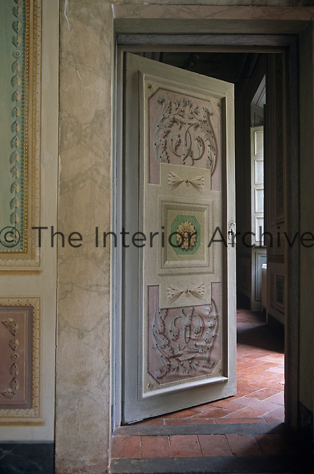 Trompe l'oeil and marbleised paint effects have been used on this open door and surrounding walls