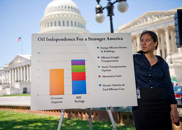 WASHINGTON, DC - June 29: Aide Sophia Yan holds a chart steady in the breeze during a news conference by her boss, Sen. Jeff Merkley, D-Ore., on the West Front of the U.S. Capitol on legislation Merkley is sponsoring that is aimed at eliminating U.S. dependence on overseas oil by 2030. (Photo by Scott J. Ferrell/Congressional Quarterly)