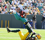Green Bay Packers' Charles Woodson, bottom, gives up a first down catch to Miami Dolphins receiver Brian Hartline during the third quarter of the game at Lambeau Field in Green Bay, Wis., on Oct. 17, 2010.
