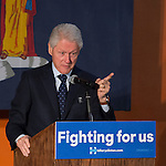 Former President Bill Clinton, pointing his index finger to audience while giving a speech, is the headline speaker as he campaigns at an Organizing Event rally in Elmont, Long Island, on behalf of his wife, Hillary Clinton, the leading Democratic presidential candidate, and former Secretary of State and U.S. Senator for New York. Podium has 'Fighting for us' slogan on sign. The New York Democratic Primary takes place April 19th.