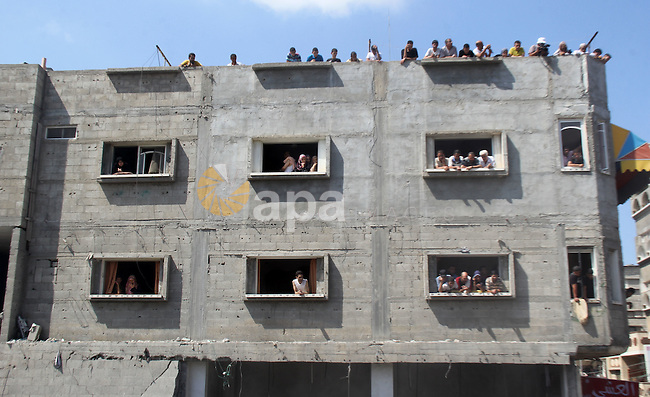 Palestinians look at the remains of al-Qassam mosque, which witnesses said was hit by an Israeli air strike, in Nuseirat refugee camp in the central Gaza Strip on August 9, 2014. Israel launched more than 20 aerial attacks in Gaza early on Saturday and militants fired several rockets at Israel in a second day of violence since a failure to extend an Egyptian-mediated truce that halted a month long war earlier this week. The Israeli military said that since midnight it had attacked more than 20 sites in the coastal enclave where Hamas Islamists are dominant, without specifying the targets. Medical officials in Gaza said two Palestinians were killed when their motorcycle was bombed and the bodies of three others were found beneath the rubble of one of three bombed mosques. The air strikes which lasted through the night also bombed three houses, and fighter planes also strafed open areas, medical officials said. Photo by Khaled al-Sabbah