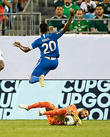 CHARLOTTE, NC - JUNE 23: Stephane Abaul #20 leaps over Jonathan Orozco #1 after Orozco makes the save during a game between Mexico and Martinique at Bank of America Stadium on June 23, 2019 in Charlotte, North Carolina.