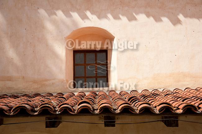 Chapel window and terra-cotta wing roof, Mission San Antonio de Padua, California.