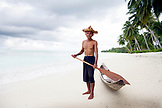 INDONESIA, Mentawai Islands, Kandui Resort, portrait of senior man holding oar by canoe at beach