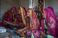 A group of women who are a part of Technoserve's kitchen garden program, gather for a training in a house in Bamanwali village, Bikaner, Rajasthan, India on October 24th, 2016. Non-profit organisation Technoserve works with guar farmer's wives in Bikaner, providing technical support and training for edible gardening, to improve the nutritional quality of their food and relieve financial stress on farming communities. Photograph by Suzanne Lee for Technoserve