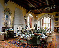 The large hall at Arundel Castle has been transformed into a comfortable living room with the use of a warm colour palette