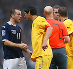 James McFadden squares up to Macedonian defenders and gets booked