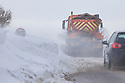 Snow ploughs struggle to clear huge snow drifts swamping country roads in the Peak District National Park, Deryshire, UK. March.