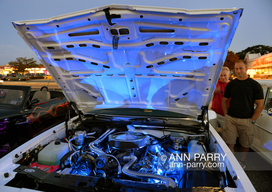 Bellmore, New York, USA. 7th August 2015. Owner JOHN GILSON, of Islip, and a visitor, look at Gilson's white 1987 Chevy Monte Carlo, with blue lights under raised hood, at the Friday Night Car Show held at the Bellmore Long Island Railroad Station Parking Lot. Gilson was one of many members of the South Side Boys auto club attending the Cruise Night. Hundreds of classic, antique, and custom cars were on view at the free weekly show, sponsored by the Chamber of Commerce of the Bellmores.