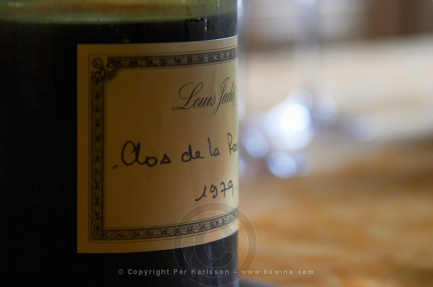 A half empty dusty old bottle with a hand written label saying Louis Jadot Clos de la Roche 1979 Grand Cru Burgundy red wine backlit back light, closeup on a dinner table, Maison Louis Jadot, Beaune Côte Cote d Or Bourgogne Burgundy Burgundian France French Europe European