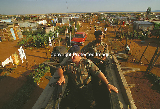 PSMILIT27009. Military. SADF Two former enemies in the new SADF. Two men with guns in truck in township. Weapons, poverty, unemployment, people on the street. .©Per - Anders Pettersson /iAfrika Photos