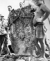 Photograph of locals with standing stone from the ahu or altar at Marae Rauhuru with carved petroglyphs of 3 turtles and geometric shapes, in the Fare Pote'e Museum at the archaeological site at Maeva village, on Huahine-Nui on the island of Huahine, in the Leeward Islands, part of the Society Islands, in French Polynesia. Maeva is thought to be an abandoned royal settlement, with many megalithic structures including marae, houses, agricultural structures, stone fish traps and fortification walls. Picture by Manuel Cohen