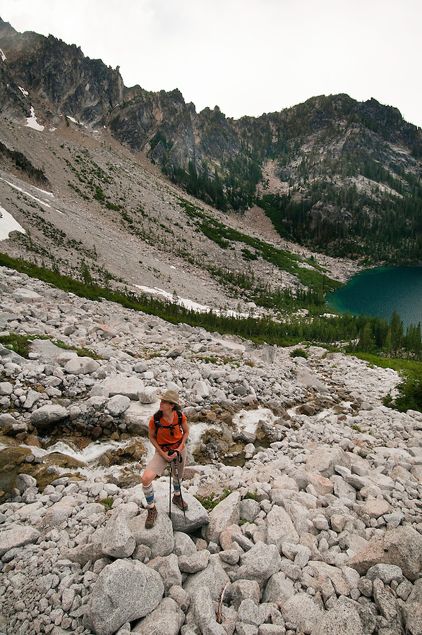 Female hiker pauses for a break on the climb up Asgard Pass above Colchuck Lake on the way into The Enchantments, Alpine Lakes Wilderness, WA.