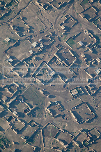 11/12/2014. Fishkhabour, Iraq. A town in ISIS held territory is seen from the door gunners position of an Iraqi Air Force Mi-171E Hip helicopter during a mission to resupply peshmerga, PKK and Yazidi refugees trapped on Mount Sinjar.<br /> <br /> Although a well publicised exodus of Yazidi refugees took place from Mount Sinjar in August 2014 many still remain on top of the 75 km long ridge-line, with estimates varying from 2000-8000 people, after a corridor kept open by Syrian-Kurdish YPG fighters collapsed during an Islamic State offensive. The mountain is now surrounded on all sides with winter closing in, the only chance of escape or supply being by Iraqi Air Force helicopters.