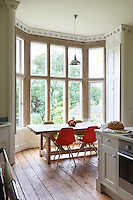 A lofty bay window makes the ideal spot for a dining area in the kitchen, furnished with a sturdy wood table and brightly coloured Eames chairs
