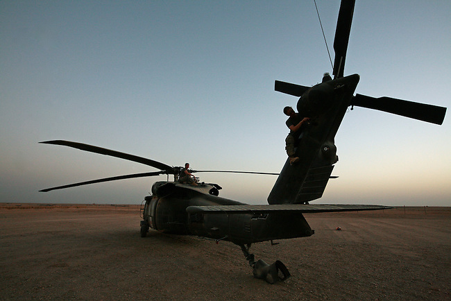 "Spc. Nicole Hyde, 20, of Aberdeen, Wash., (foreground) and Chief Warrant Officer Jesse Russell, 33, a self-described ""Air Force brat"" perform maintenance on their UH-60 Blackhawk helicopter during a break between medevac missions in Helmand province, southern Afghanistan. July 17, 2009. DREW BROWN/STARS AND STRIPES"