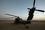 """Spc. Nicole Hyde, 20, of Aberdeen, Wash., (foreground) and Chief Warrant Officer Jesse Russell, 33, a self-described """"Air Force brat"""" perform maintenance on their UH-60 Blackhawk helicopter during a break between medevac missions in Helmand province, southern Afghanistan. July 17, 2009. DREW BROWN/STARS AND STRIPES"""