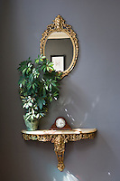 In the entrance hall an antique gilded mirror with a matching mable-topped table displays an antique clock and houseplant