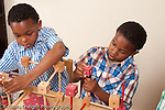 Brothers ages 8 and 6 playing with wood stick and cube construction toy horizontal