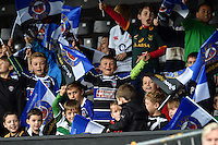 Young Bath Rugby fans in the crowd wave flags in support. Bath Rugby Captain's Run on October 30, 2015 at the Recreation Ground in Bath, England. Photo by: Patrick Khachfe / Onside Images