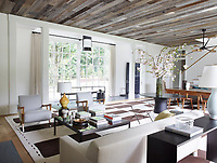 The living area is both dramatic and relaxed with just the right contrast between the classic architecture and the minimalist furnishings. The lofty ceiling is clad in ravaged barn siding and the floor is laid with wide-plank oak. The armchairs are by Studio Van den Akker, the cocktail table is from Holly Hunt, and the sofa is a custom design; the mirror is from Maison Gerard, the rug is by Joseph Carini Carpets, and the walls are covered in hand-trowelled plaster.