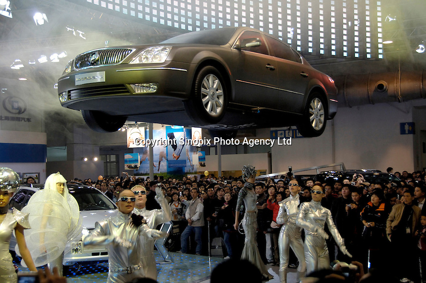 Visitors take pictures of a replica car of GM Lacrosseat at the Beijing Auto Show..25 Nov 2006
