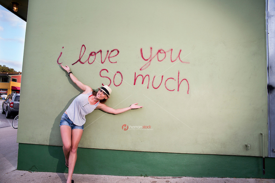 "An local Austin woman poses in front of the famous ""I love you so much"" mural on South Congress in Austin, Texas."