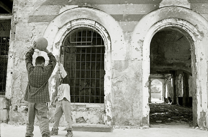 Two boys play basketball outside a ruined building in Mostar, Bosnia Herzegovina.
