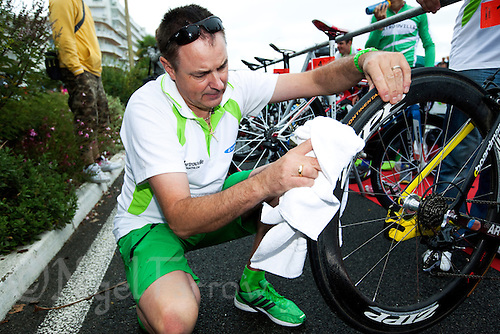 17 SEP 2011 - LA BAULE, FRA - EC Sartrouville team manager Eric Dubois wipe his competitors bike tyres in transition before the start of the final round of the men's French Grand Prix Series at the Triathlon Audencia in La Baule, France (PHOTO (C) NIGEL FARROW)