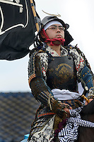 Participant in the parade, Somanomaoi Festival, Minami-soma City, Fukushima Prefecture, Japan, July 28, 2013. During the four-day-long Somanomaoi Festival members of old samurai families ride horseback through the town in traditional armour.  They also take conduct ceremonies at local shrines, take part in horse races, and compete on horseback to catch a flag launched into the air by fireworks.