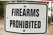"California, USA. Bent damaged ""Firearms Prohibited"" road sign."
