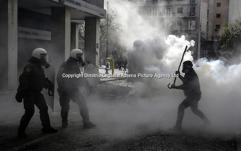 Pictured: A farmer with a stick attacks riot police officers Friday 12 February 2016<br /> Re: Violent clashes between farmers and riot police outside the Ministry of Agricultural Development in Athens, Greece. The farmers travelled from Crete to protest against pension and welfrae reforms proposed by the Greek government,