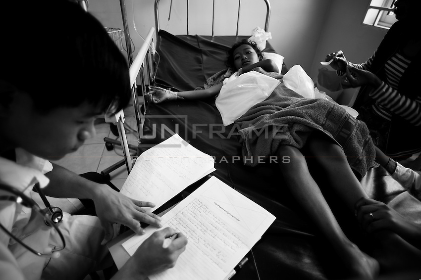 Young Cambodian doctor performing medical examination. Because of the lack of doctors it is common practice for Cambodia to assign graduated students to a full time job in village health centers.