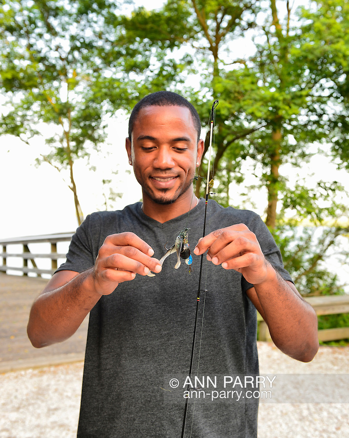 South Merrick, New York, U.S. 14th July 2013. LUIS HERRERA, from the Bronx, is holding out the fishing lures he used on the fishing pier at Levy Park & Preserve. He and his friends didn't catch any fish, but the South Shore winds helped keep them comfortable, as National Weather Service extended its Heat Advisory in Long Island, New York, through to next day. A dangerous heatwave was spreading throughout the Northeast, 92 degrees Fahrenheit, 33 degrees Celsius.