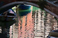 Reflections under a bridge of the pastel colored buildings and boats. Painted effect. (Photo by Travel Photographer Matt Considine)
