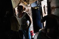 A Cuban woman, the Palo religion follower, passes through her house in Santiago de Cuba, Cuba, August 3, 2009. The Palo religion (Las Reglas de Congo) belongs to the group of syncretic religions which developed in Cuba amongst the black slaves, originally brought from Congo during the colonial period. Palo, having its roots in spiritual concepts of the indigenous people in Africa, worships the spirits and natural powers but can often give them faces and names known from the Christian dogma. Although there have been strong religious restrictions during the decades of the Cuban Revolution, the majority of Cubans still consult their problems with practitioners of some Afro Cuban religion.